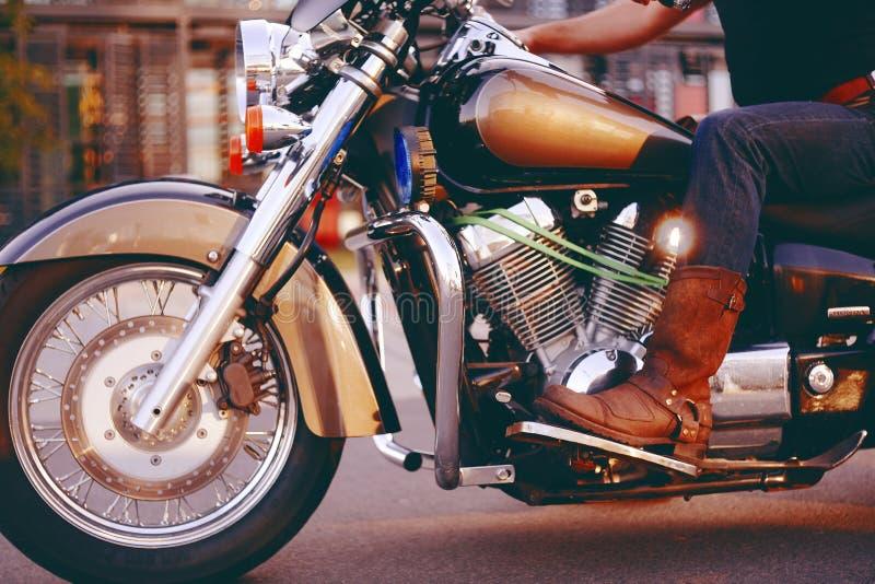Guida del motociclista su un motociclo Vista dal basso delle gambe in stivali di cuoio Un uomo vicino al centro dell'ufficio su u immagine stock