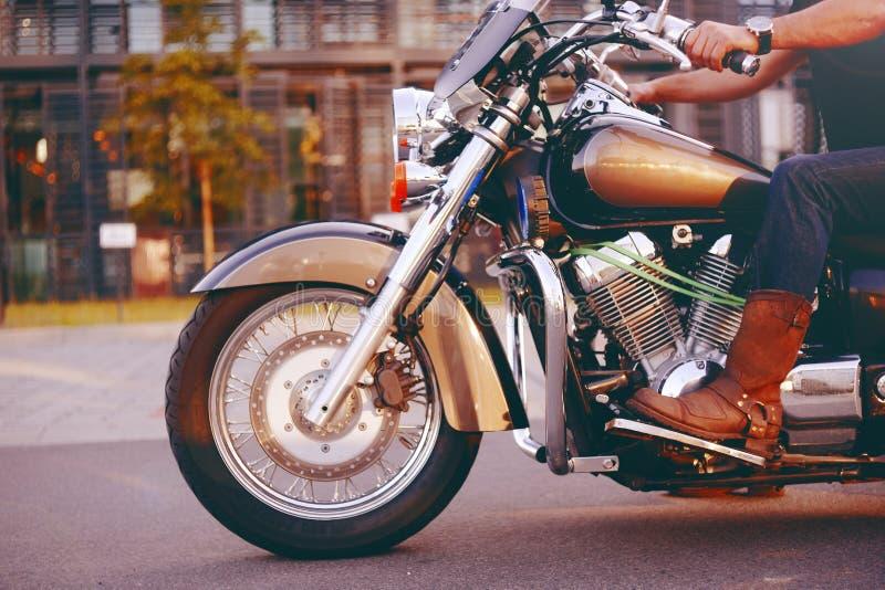 Guida del motociclista su un motociclo Vista dal basso delle gambe in stivali di cuoio Un uomo vicino al centro dell'ufficio su u immagini stock