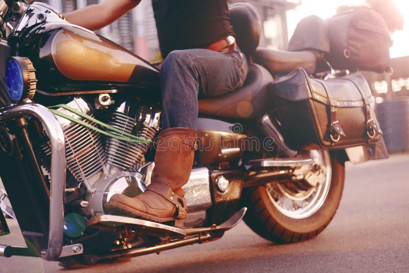 Guida del motociclista su un motociclo Vista dal basso delle gambe in stivali di cuoio Un uomo vicino al centro dell'ufficio su u fotografia stock libera da diritti