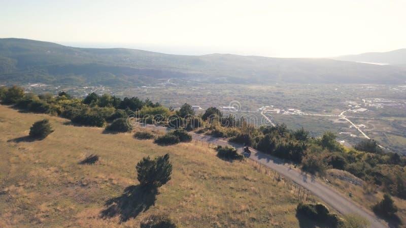 Guida del motociclista sulla strada rurale in montagne azione Punto di vista superiore del motociclista di guida in bomber nero s fotografia stock