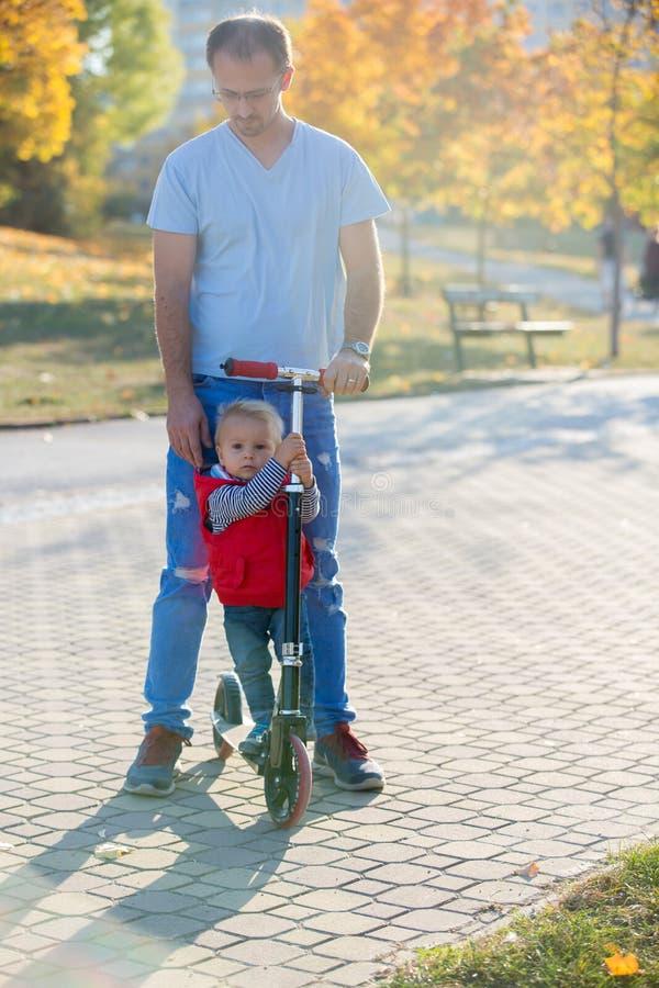 Guida del padre con il suo motorino del figlio del bambino in un parco di autunno fotografia stock