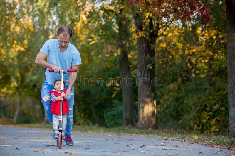 Guida del padre con il suo motorino del figlio del bambino in un parco di autunno immagine stock libera da diritti
