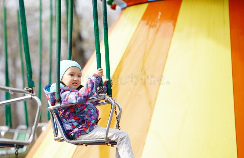 Guida del piccolo bambino su un'oscillazione chaing immagini stock