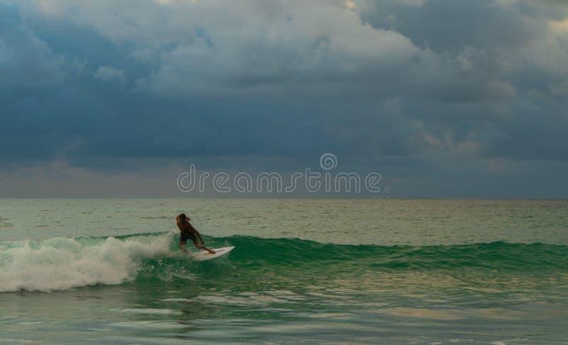 Guida del surfista lungo l'onda immagine stock