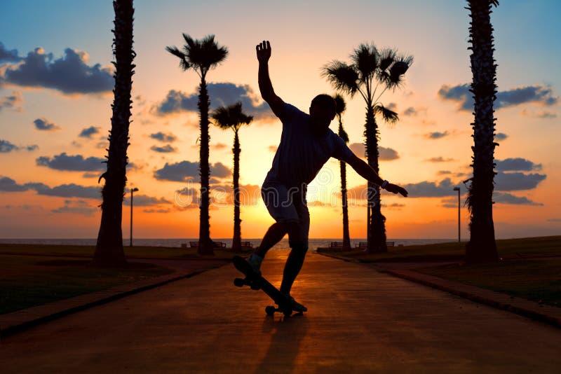 Guida dell'uomo sul pattino nel tramonto immagine stock