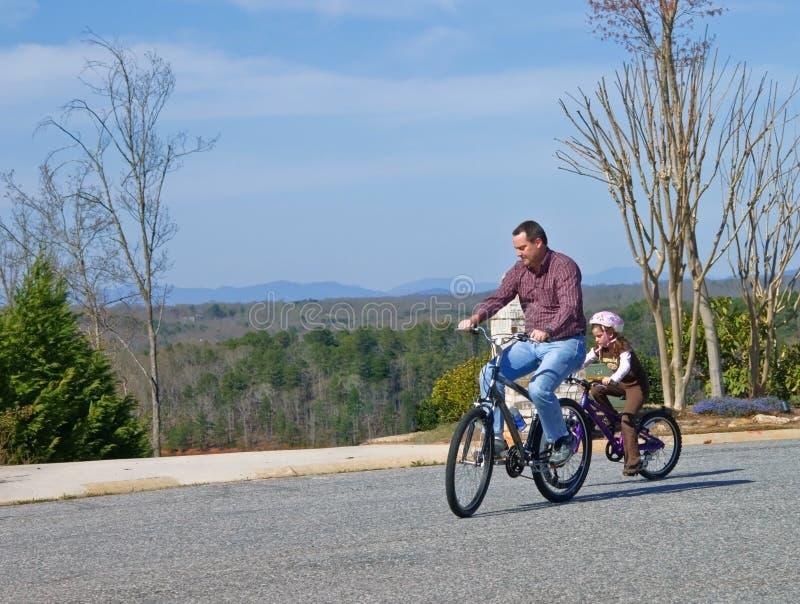 Guida della bici della figlia e del padre fotografia stock libera da diritti