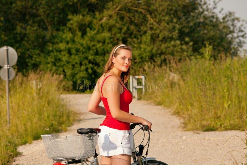 Guida della donna la sua bicicletta in estate immagine stock