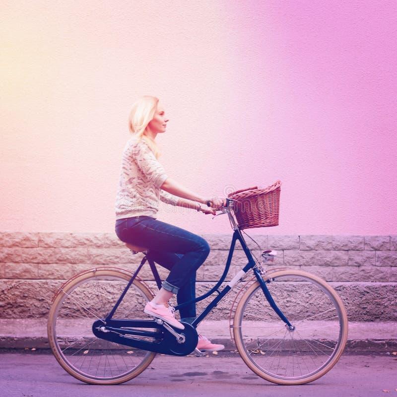 Guida della donna sulla bicicletta d'annata con il canestro fotografie stock libere da diritti