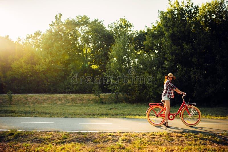 Guida della donna sulla bicicletta d'annata nel parco di estate fotografie stock libere da diritti
