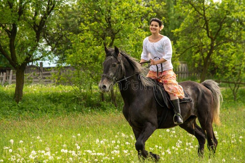 Guida della giovane donna sul cavallo bello, divertendosi nell'ora legale, campagna della Romania immagini stock libere da diritti
