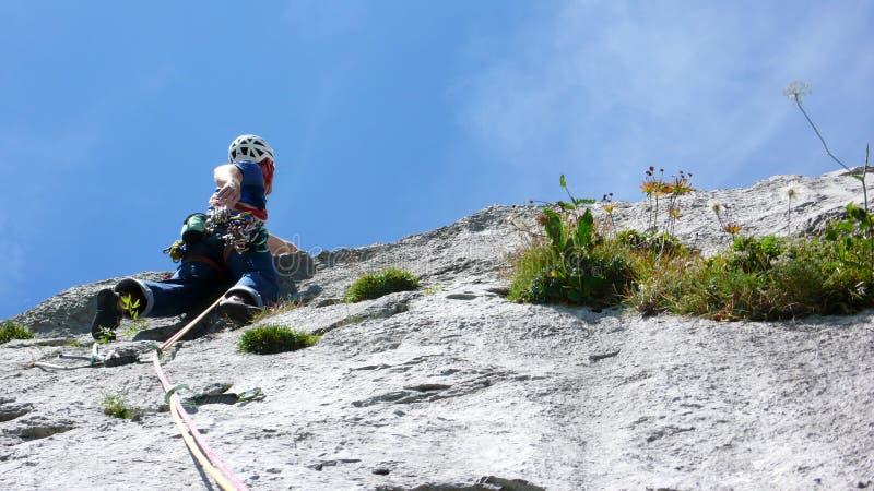 Guida della montagna che scala un passo ripido della lastra di un itinerario di scalata di hard rock nelle alpi della Svizzera fotografie stock