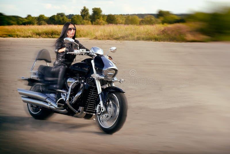 Guida della ragazza del motociclista su un motociclo immagini stock libere da diritti