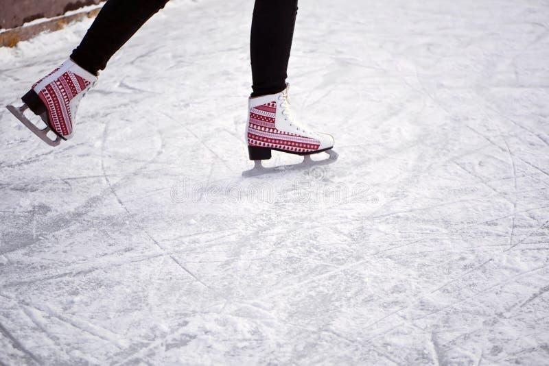 Guida della ragazza su una pista di pattinaggio sul ghiaccio Ghiaccio e pattini I piedi dell'uomo in pattini immagine stock