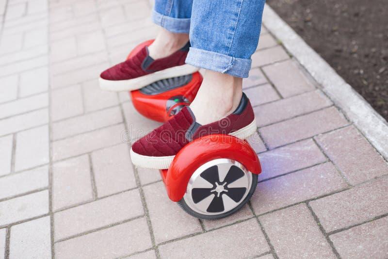 Guida della ragazza sul motorino mini elettrico rosso moderno di librazione o segway del bordo fotografia stock