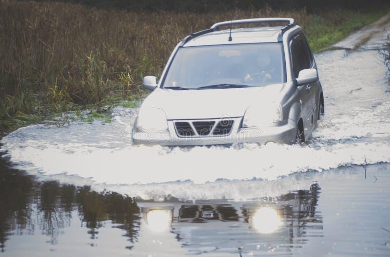 Guida di veicoli attraverso l'acqua immagine stock