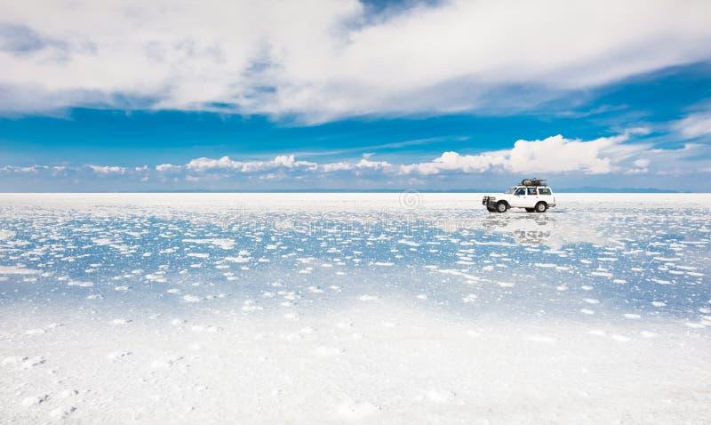 Guida di veicoli fuori strada attraverso il piano del sale di Salar de Uyuni in Bolivia immagine stock libera da diritti