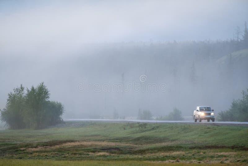 Guida di veicoli lungo la strada campestre nebbiosa fotografie stock libere da diritti