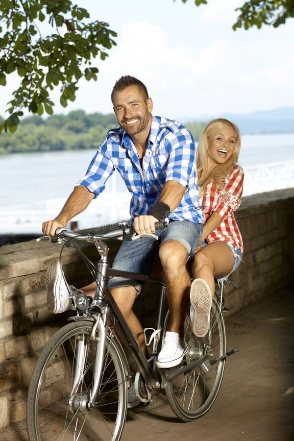 Guida felice delle coppie sulla bicicletta all'aperto immagine stock