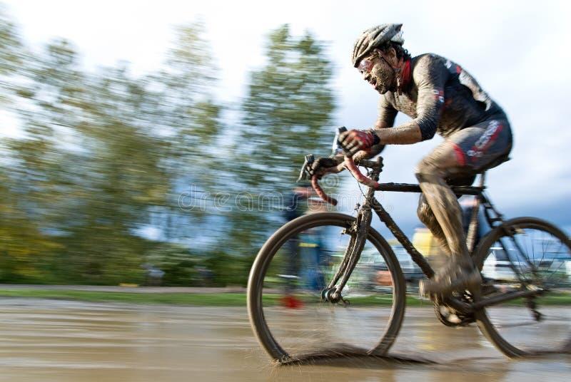 Guida maschio del ciclista attraverso una pozza di fango immagini stock libere da diritti