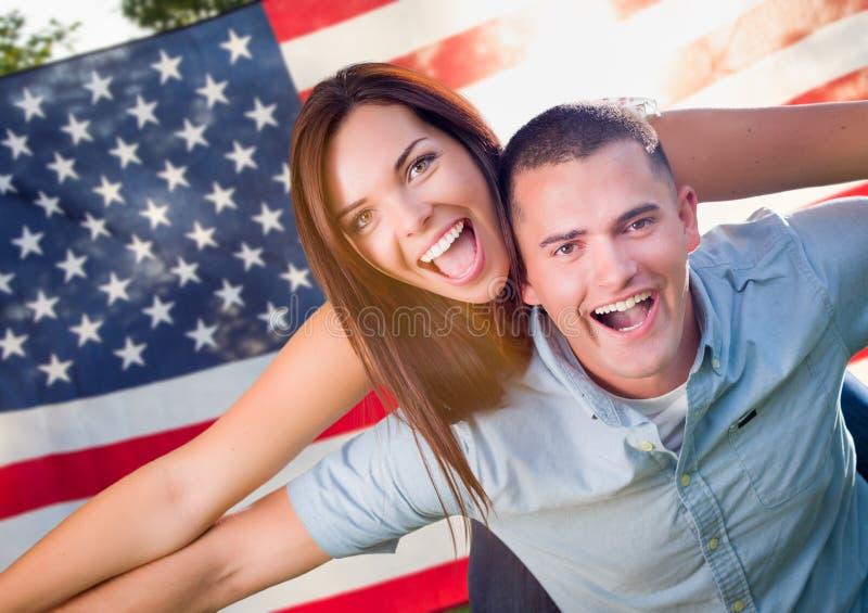 Guida militare di porcellino delle coppie davanti alla bandiera americana fotografia stock