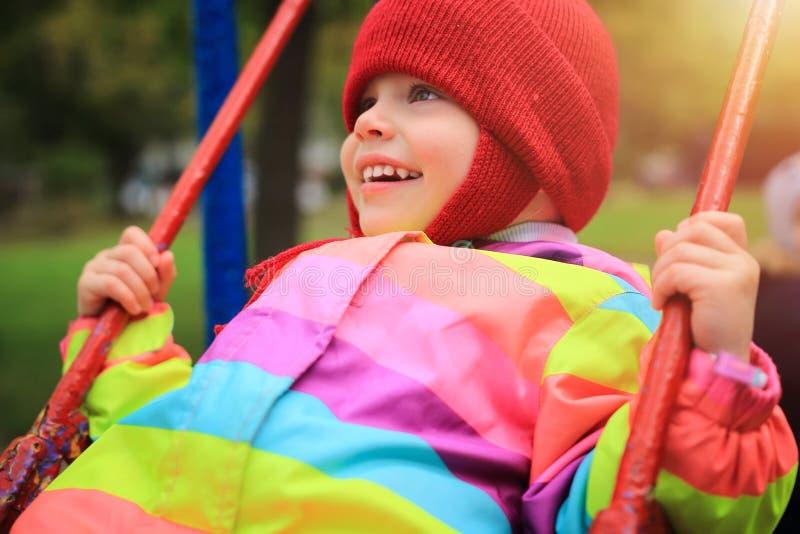 Guida sorridente felice della bambina sull'oscillazione Bambino allegro sul carosello Piccolo giri del bambino su oscillazione su fotografia stock libera da diritti