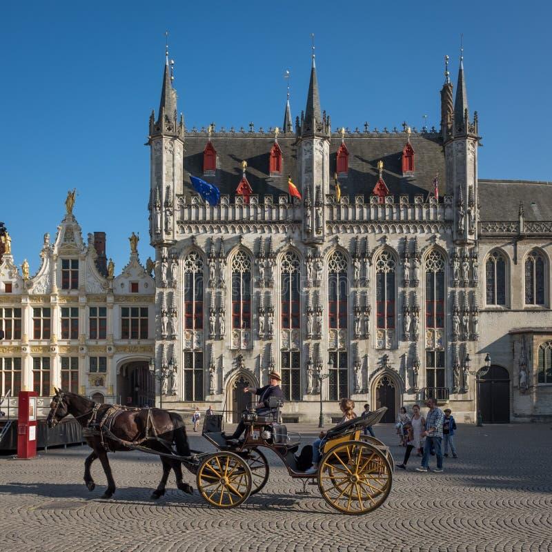 """Guida turistica e turisti sul carretto e sul cavallo sul quadrato """"di Burg """"a Bruges, Belgio immagine stock"""