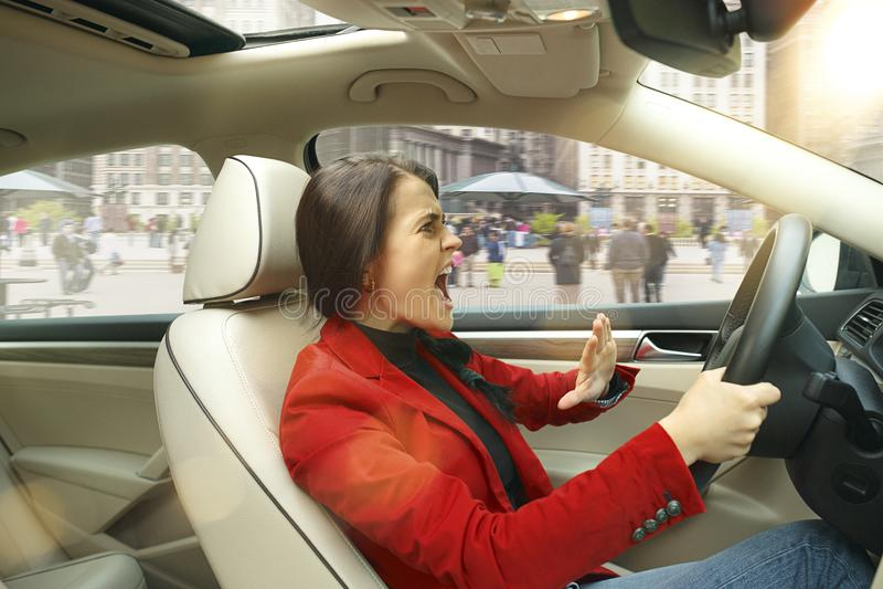 Guidando intorno alla città Giovane donna attraente che conduce un'automobile immagini stock libere da diritti