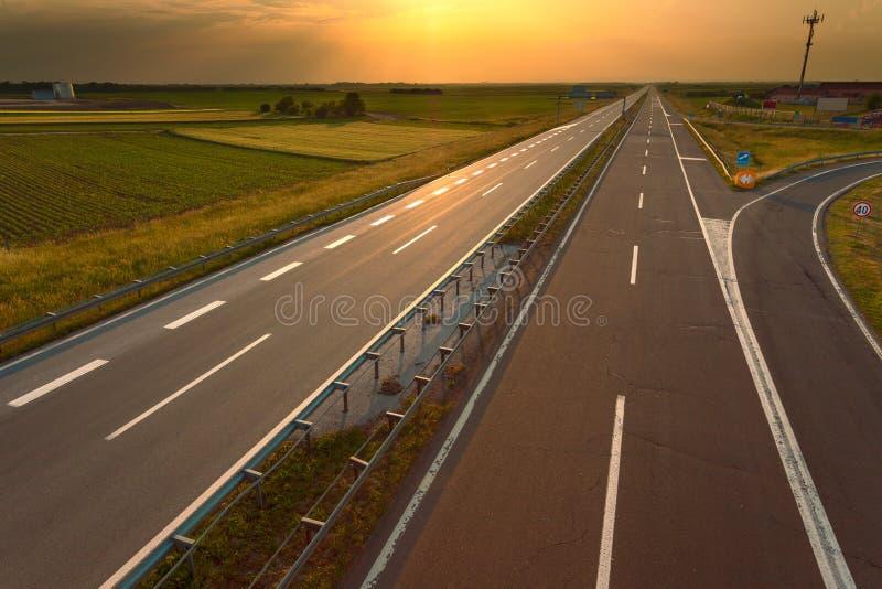 Guidando su un'autostrada vuota al tramonto fotografia stock