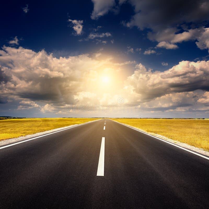 Guidando su una nuova strada asfaltata vuota al tramonto fotografie stock libere da diritti