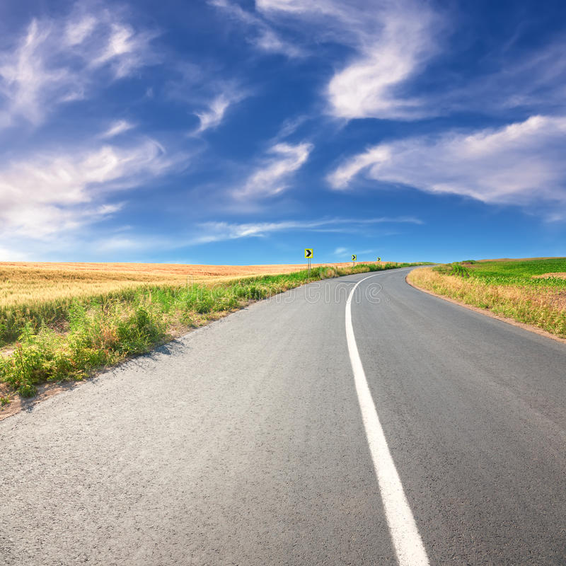 Guidando su una strada asfaltata vuota al giorno soleggiato fotografie stock libere da diritti