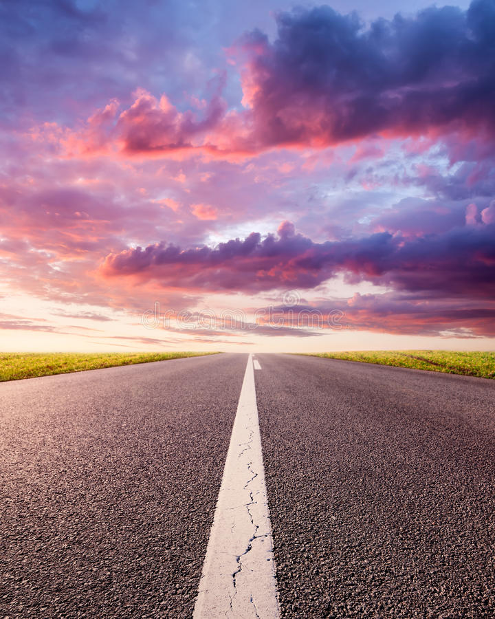 Guidando su una strada asfaltata vuota al tramonto fotografia stock libera da diritti