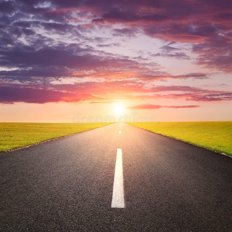 Guidando su una strada vuota al sunsrise immagini stock