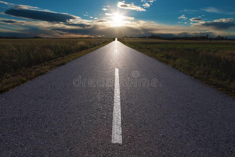 Guidando su una strada vuota verso il tramonto immagine stock libera da diritti