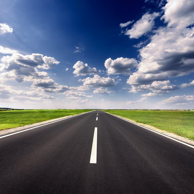 Guidando sulla strada asfaltata vuota al giorno soleggiato idilliaco fotografia stock