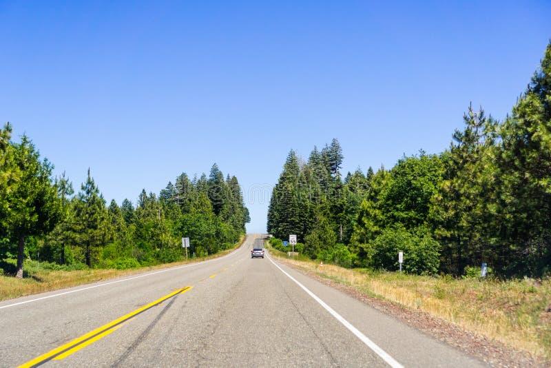 Guidando sulla strada principale fra Redding e Burney un giorno di estate soleggiato, la contea di Shasta, California del Nord immagini stock libere da diritti