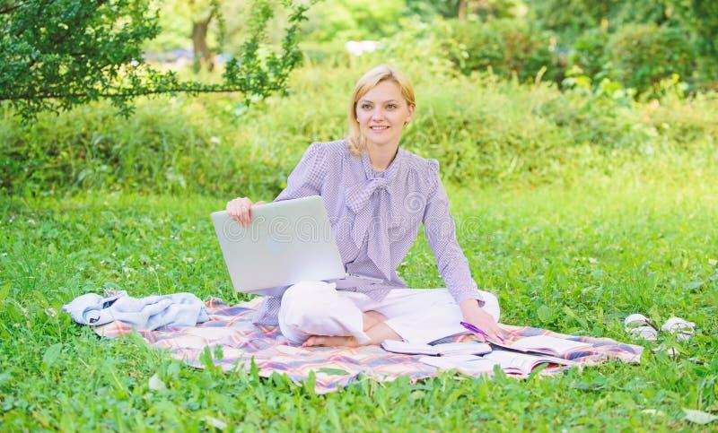 Guide commen?ant la carri?re ind?pendante La femme avec l'ordinateur portable s'asseyent sur le pr? d'herbe de couverture ?tapes  images libres de droits