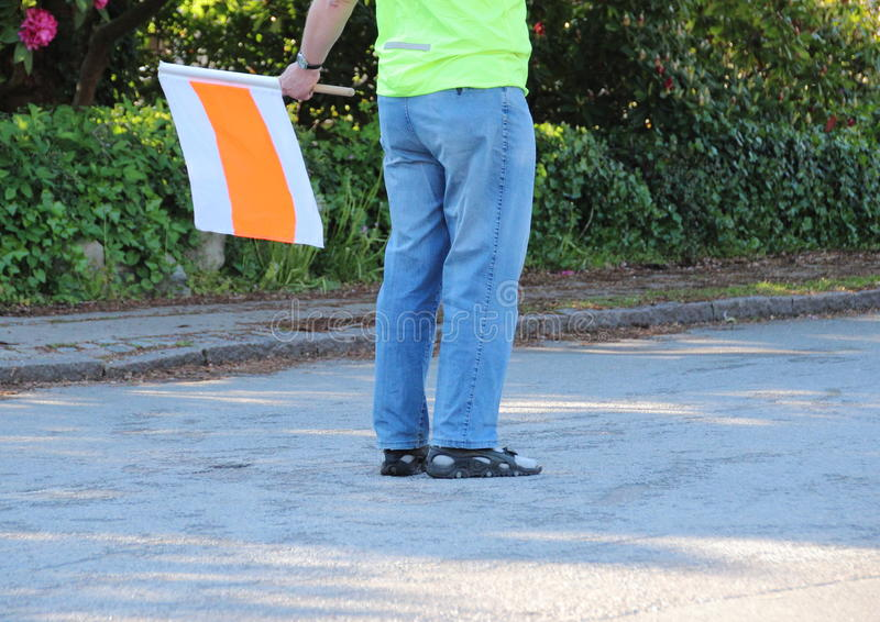 Guide du trafic avec le drapeau à la course courante photo stock