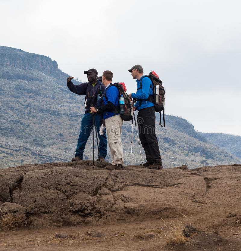 Guide instructs hiking tourists on mountain (2) stock photos