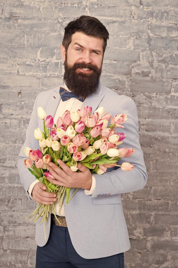 Guide for modern man. Romantic man with flowers. Romantic gift. Macho getting ready romantic date. Tulips for sweetheart. Man well groomed tuxedo bow tie hold stock photo