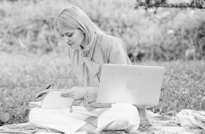 Guide starting freelance career. Business lady freelance work outdoors. Woman with laptop sit on rug grass meadow. Steps royalty free stock photo