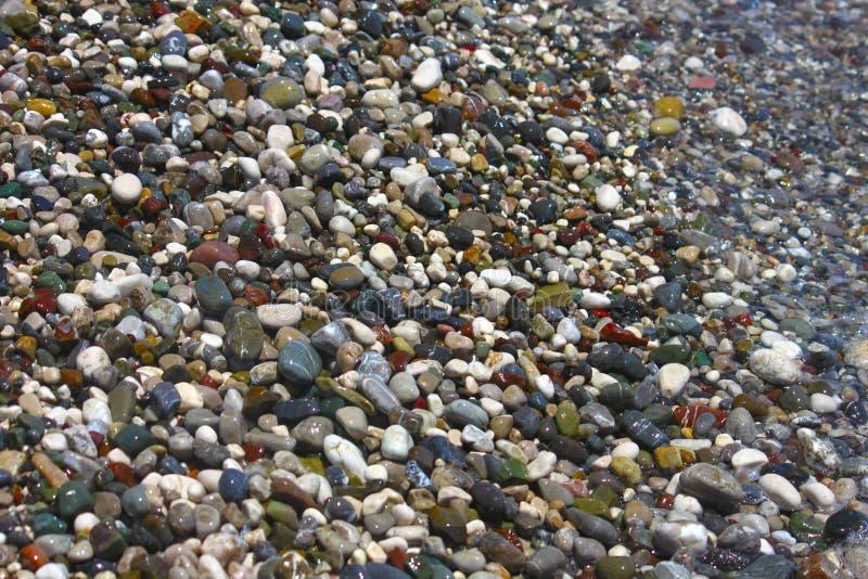 Guijarros multicolores brillantes en la playa en el mar Mediterráneo fotos de archivo