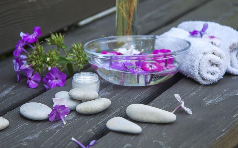 guijarros redondos del mar del balneario y flores rosadas en fondo de madera foto de archivo libre de regalías