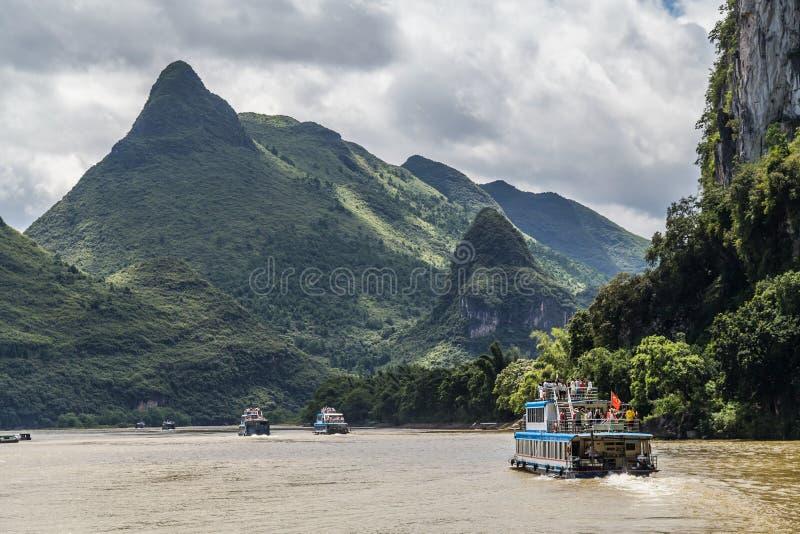 Guilin, China - circa julio de 2015: El barco de la travesía navega entre las montañas del karst y los picos de la piedra caliza  imagen de archivo libre de regalías