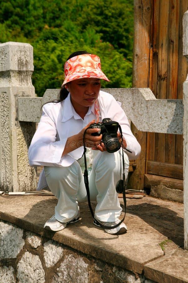 Guilin, China - 16 de julio de 2018: Un fotógrafo de sexo femenino chino que hace las fotos durante el descenso de la montaña de  imagen de archivo libre de regalías