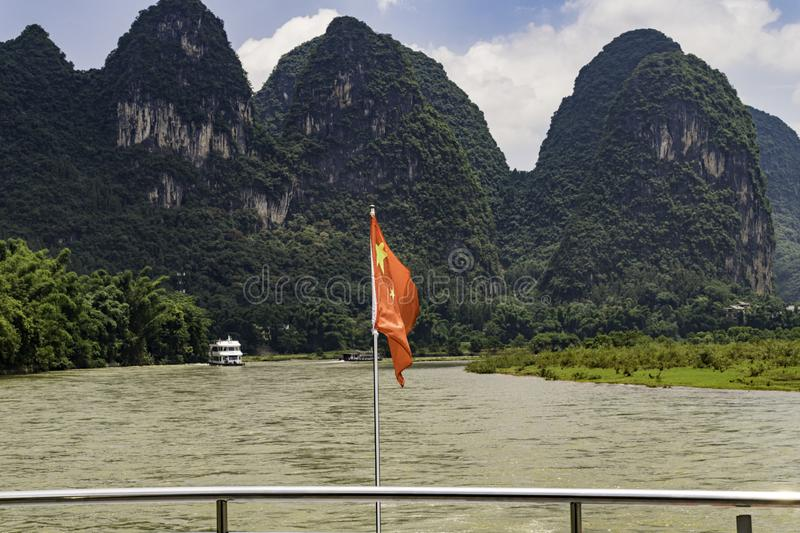 Guilin China famous karst mountains tall day river cruise Lijiang boat. Karst mountains of limestone are sharp, tall mountains formed from receding water of the stock images