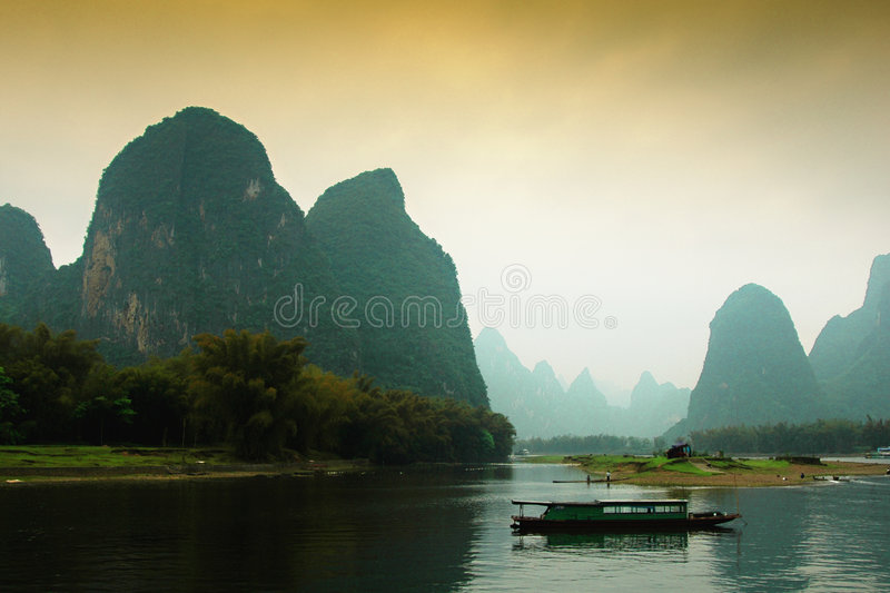 Guilin china landscape. A fishing boat along water of Guilin China, surrounded by what is frequently called 'grotesque' mountains