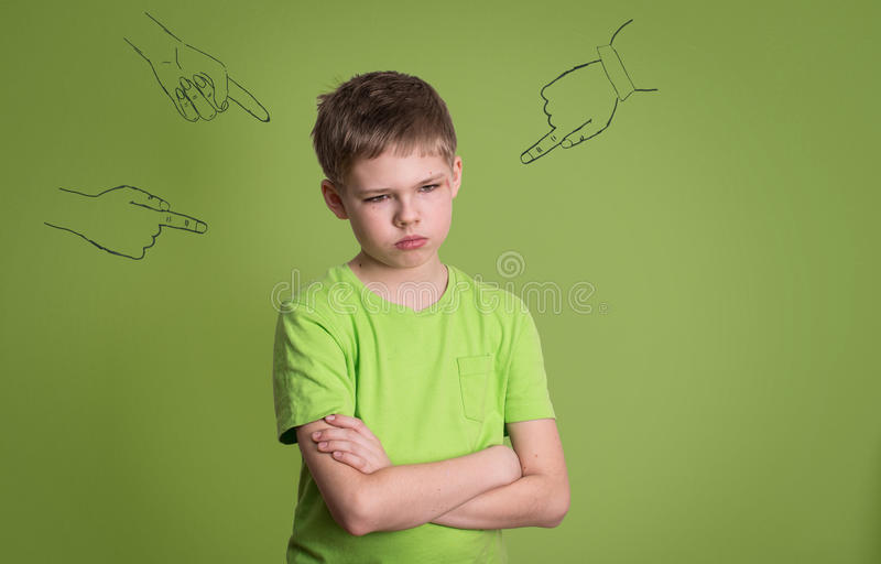 Guilty. Concept of accusation guilty person teen boy. Sad upset. Kid looking down with arms crossed, sketch fingers hands pointing at him. Human face expression stock photography