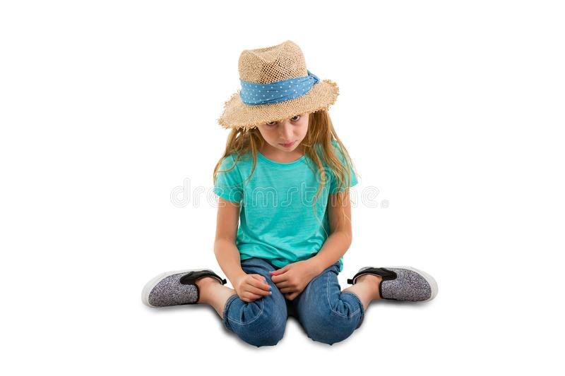 Guilty little girl sitting with her head bowed. Looking very contrite as she gazes down at the floor isolated on white with copy space stock images