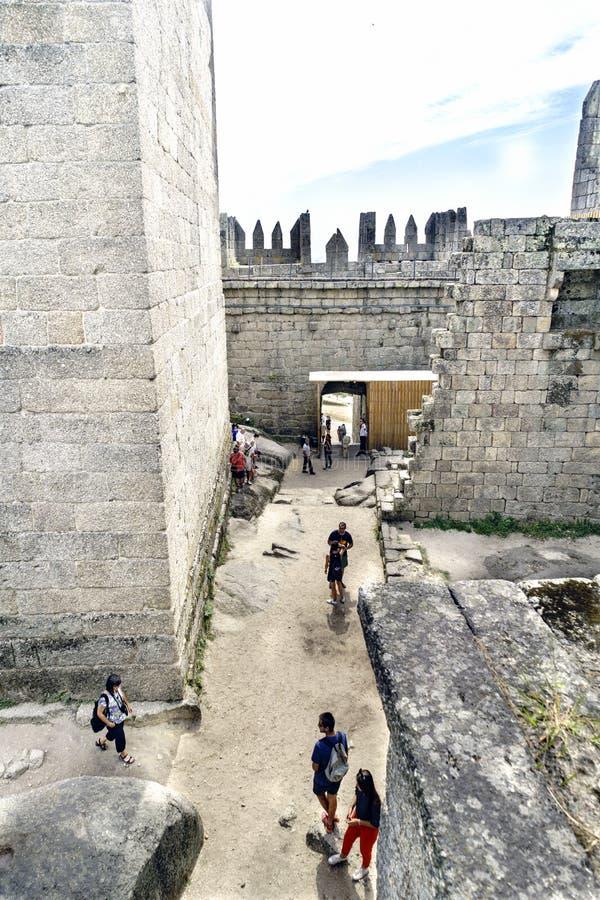 Guimaraes, Portogallo 14 agosto 2017: I turisti che visitano i corridoi interni di re Afonso Henriques fortificano dall'undicesim immagine stock libera da diritti