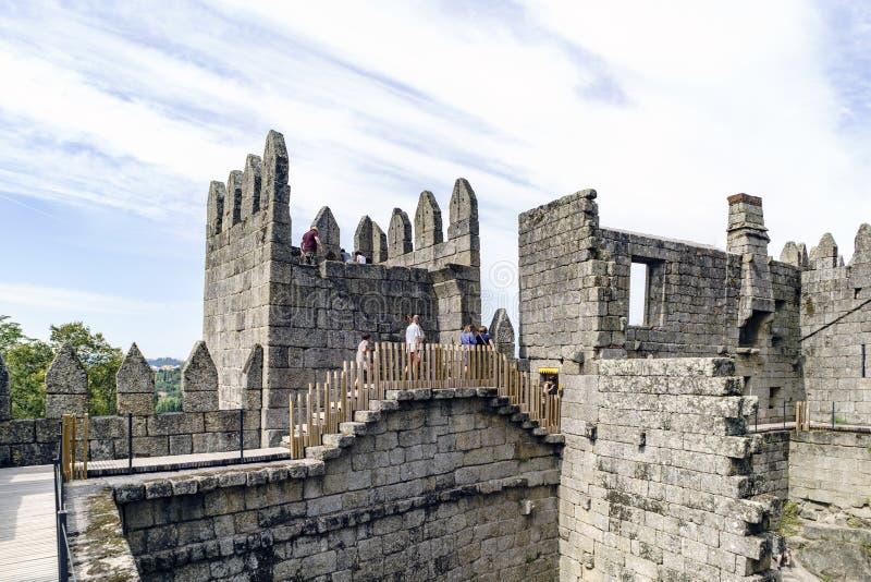 Guimaraes, Portugal 14 augustus, 2017: De mensen die door de muren van het kasteel van Koning Afonso Henriques lopen bouwden elev royalty-vrije stock fotografie